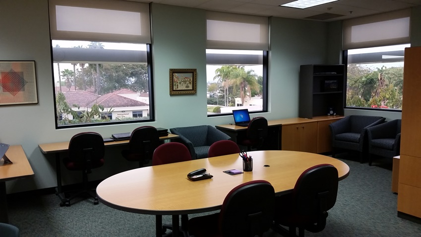 Large conference table with chairs. Laptops are available for use in this room.