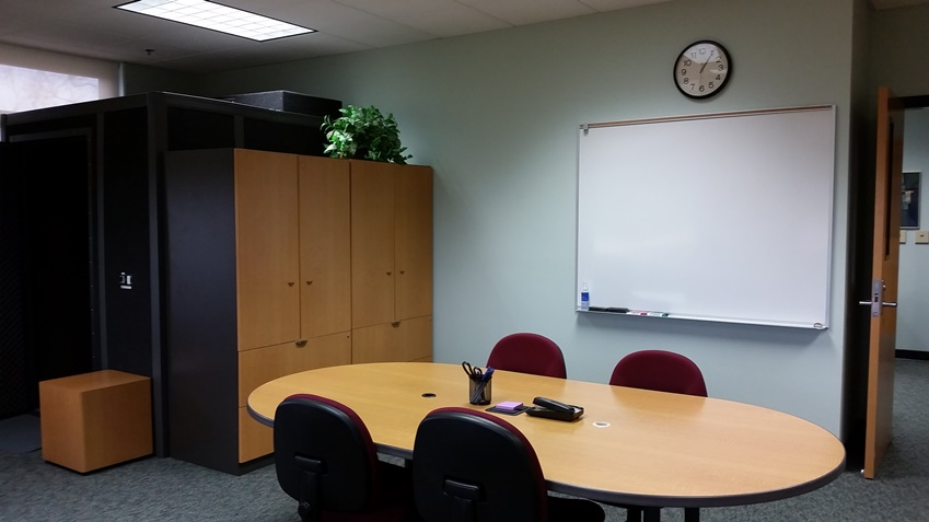 View of the whiteboard, conference table, recording booth, and back cabinets in 1253B.