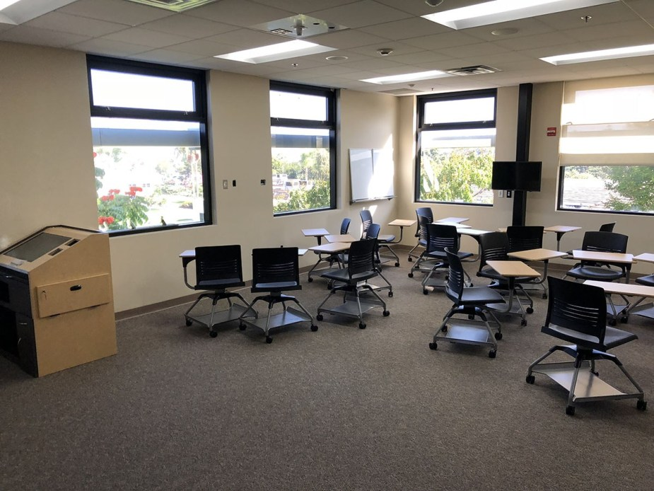 Collaboration Studio features a standard smart classroom podium, movable desks, and three monitors for group activities.